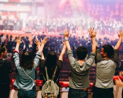 people raising their arms to worship